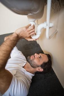 Водопроводчик, устанавливающий раковину в ванной комнате