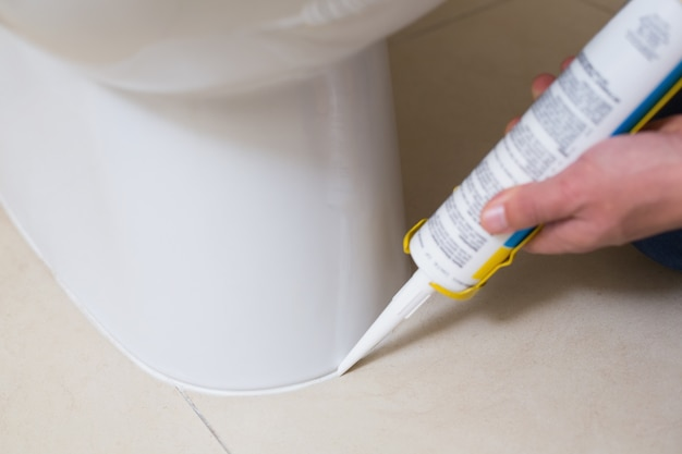 Plumber fixing toilet in a washroom with silicone cartridge
