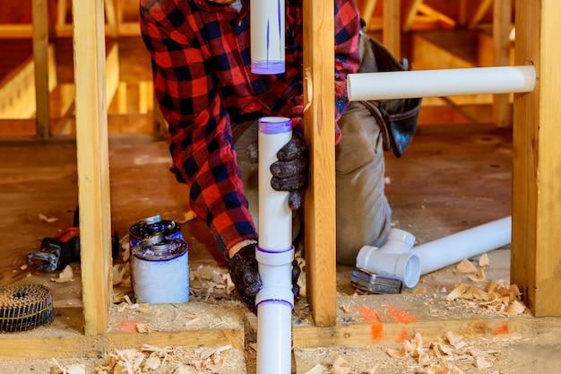 配管工の接着剤の白いpvcパイプ、新しい家に新しいプラスチックの排水管を取り付ける