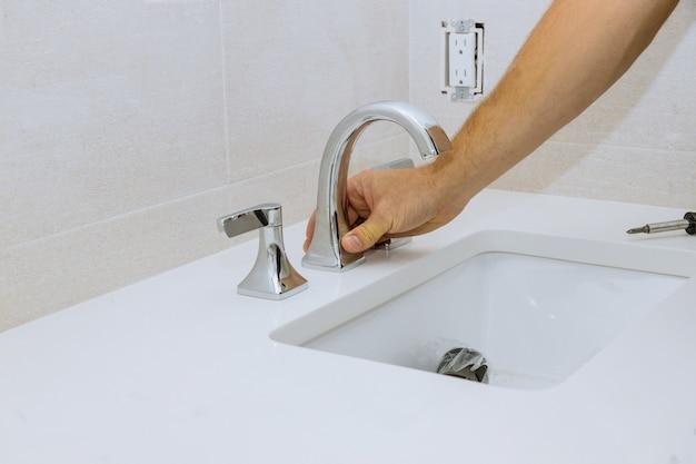 配管工は浴室で仕事をし、配管修理サービスは新しい蛇口を流しに