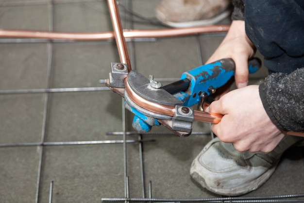 Plumber hands bends copper pipes by pipe bender