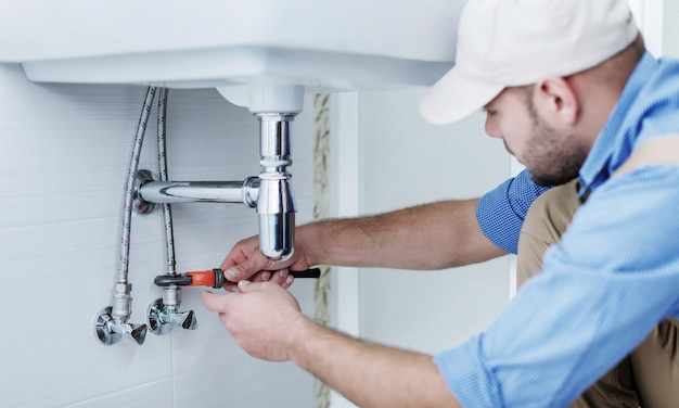 Plumber hands fixing water tap on background