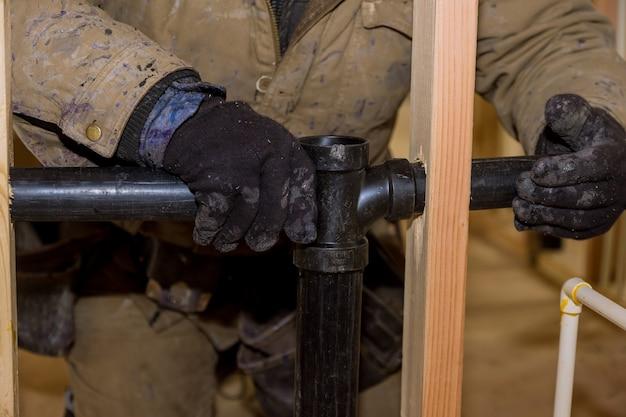 配管工が2枚のプラスチック排水管を接着剤で手に入れ、pvcパイプを排水し、新しいバスルームを閉じます