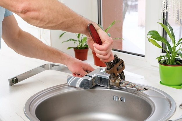 Plumber hands removes the old faucet from the sink with an adjustable wrench