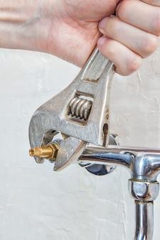 配管工のモンキーレンチを使用して蛇口バルブをねじ込む配管工の手。