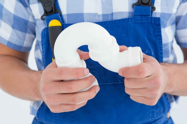 Plumber holding sink pipe on white background