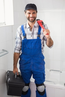Plumber holding wrench and toolbox