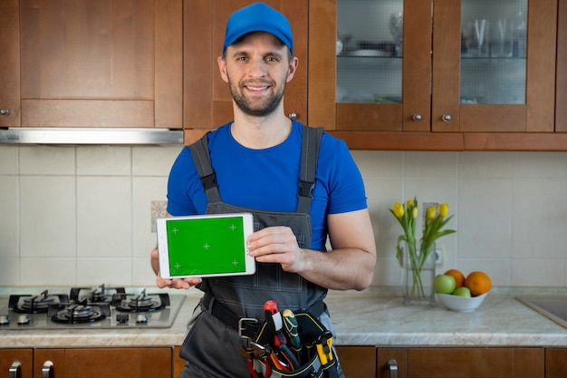 Plumber holds a digital tablet with a green screen in the kitchen