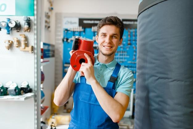 Plumber holds water pump, plumbering store
