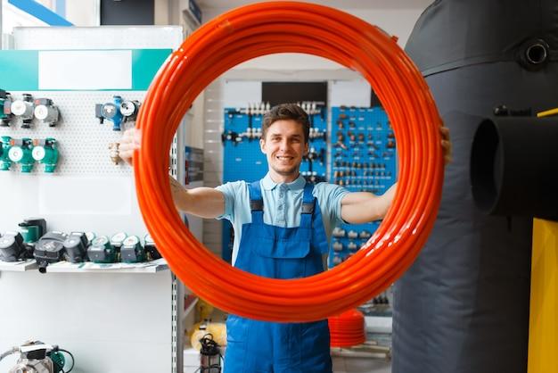 制服を着た配管工は、配管店でパイプ ロールを保持します。店で衛生工学を買う男