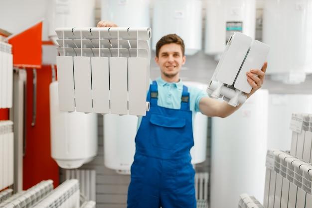 制服を着た配管工は、配管店の給湯ラジエーターを示しています。店で衛生工学を買う男