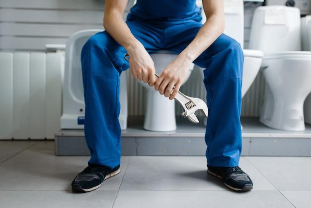 配管工店のショーケースでトイレに座っている制服を着た配管工。店で衛生工学の道具や設備を買う男