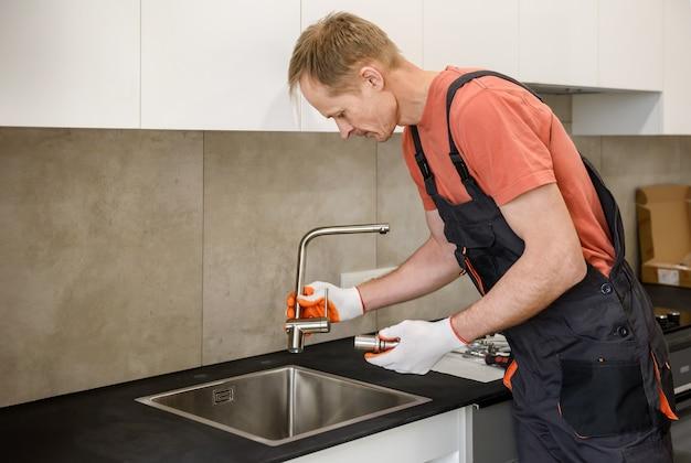 台所の流しに蛇口を設置する配管工