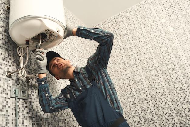 전기 난방 보일러를 설치 하는 배관공은 전기 난방을 설정 하는 유니폼에 젊은 핸디