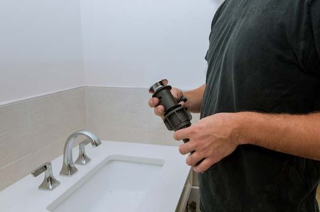 Plumber installing new drain hands worker close up