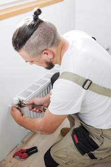 새로운 강철 온수 중앙 난방 라디에이터를 설치 하는 배관공
