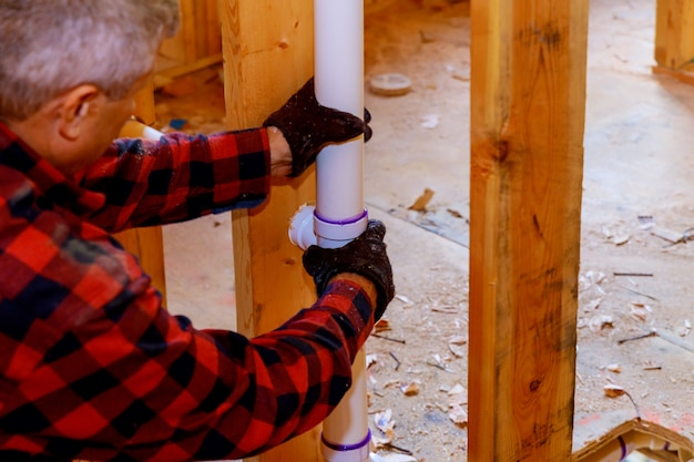 Plumber installing pvc pipe at under construction of the house