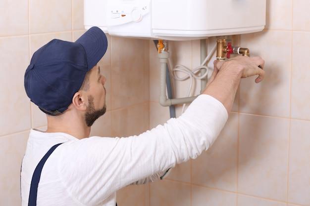 욕실에 온수기를 설치하는 배관공