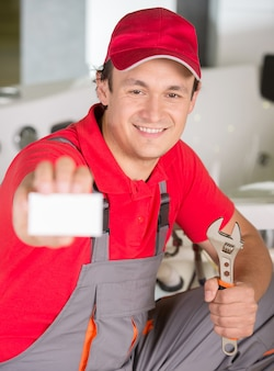 Plumber is holding spanner in hand and showing business card