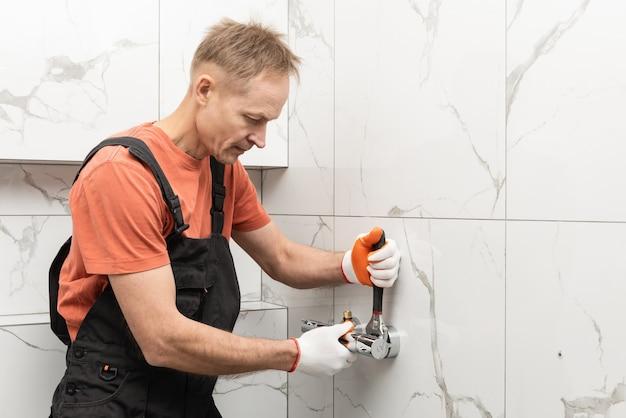 配管工は、モンキーレンチ付きのシャワー水栓を設置しています。