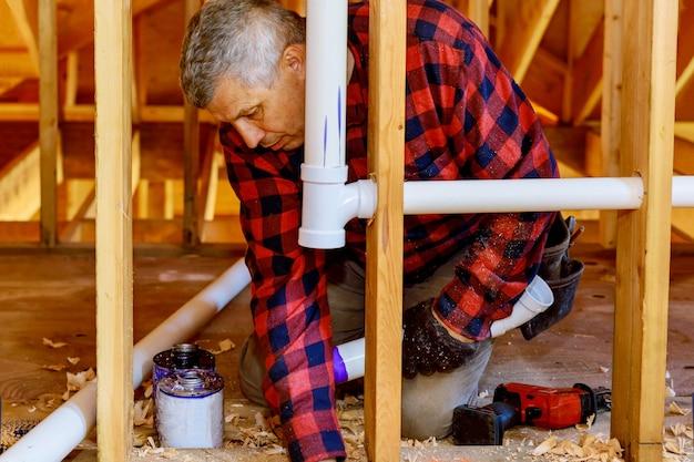 建設中の新しい家の下で排水管用の接着剤でプラスチックパイプを結合する配管工