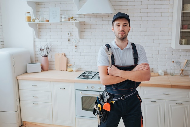 Plumber in the kitchen with tools belt