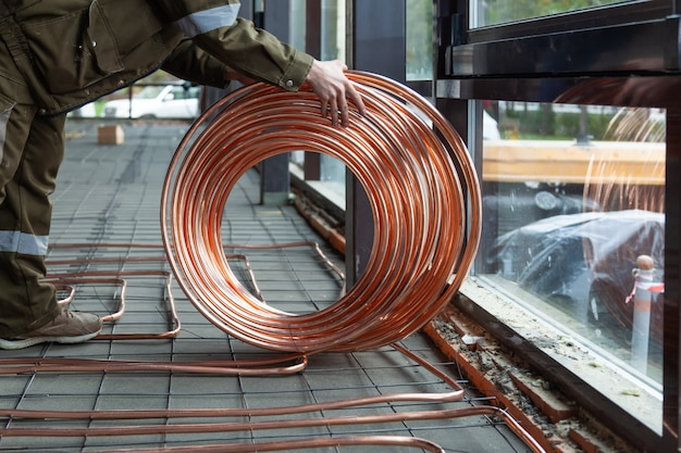 Plumber laying copper pipes on floor with warm heating