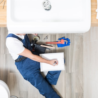 Plumber lying and writing in tablet