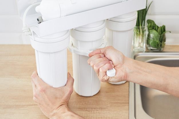 Plumber or man hand replace a water filter cartridges. fix purification osmosis system.