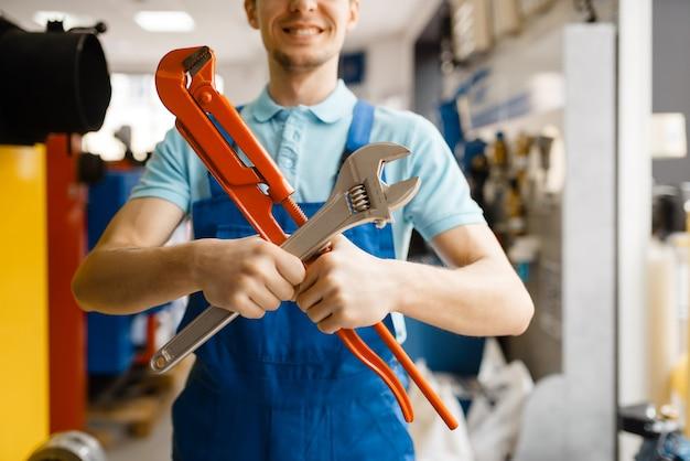 配管工店のショーケースでパイプ レンチを使ってポーズをとる配管工。店で衛生工学の道具や設備を買う男