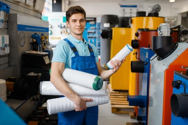 配管工店のショーケースでポーズをとる配管工。店で衛生工学の道具や設備を買う男
