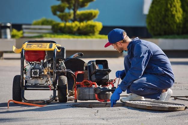 配管工は下水道の問題を解決する準備をしています。トラブルシューティングの修復作業。