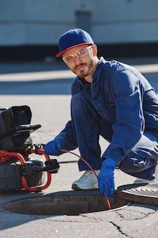 配管工は、パイプ検査用のポータブルカメラで下水道の問題を解決する準備をしています