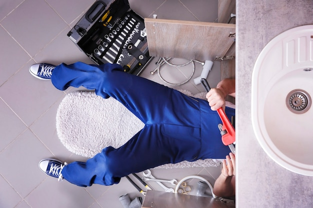 Plumber repairing sink pipes in kitchen