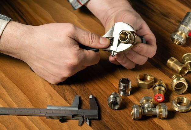 Сантехник прикручивает латунный фитинг к клапану с помощью сантехнического ключа. руки мастера крупным планом