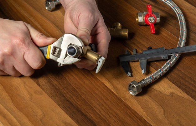 The plumber screws the brass fitting onto the valve with a plumbing wrench