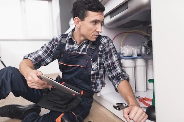 Сантехник сидит рядом с кухонной раковиной на полу.