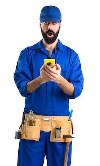 Водопроводчик разговаривает с мобильным телефоном
