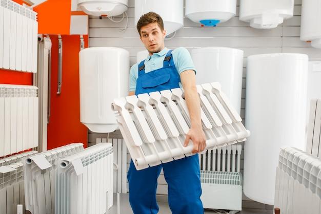 Plumber in uniform holds water heating radiator at showcase in plumbering store.