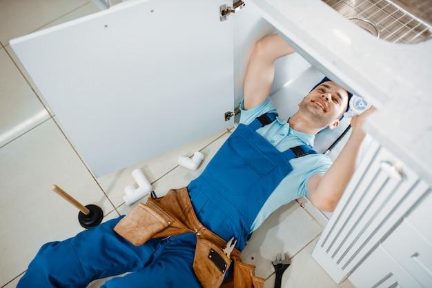 Plumber in uniform installing drain pipe, top view