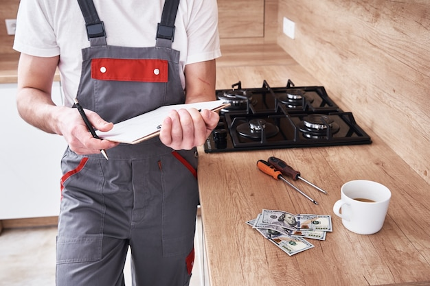 Plumber in uniform signs a contract for services in the kitchen