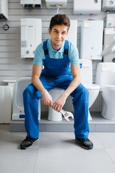 Plumber in uniform sitting on toilet at the showcase in plumbering store