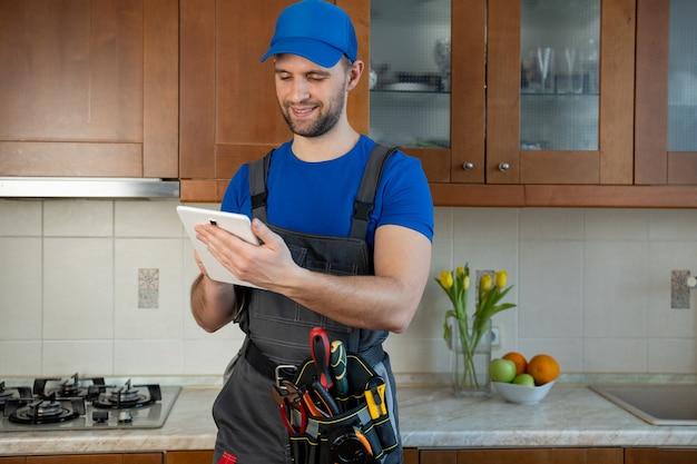 Сантехник с поясом для инструментов с различными инструментами, используя планшет во время работы на кухне
