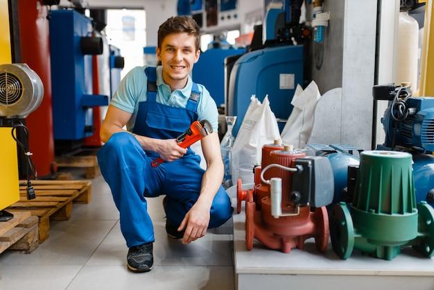 配管工店のショーケースでパイプ レンチを使った配管工。店で衛生工学を購入する男性、ポンプ、給湯器の選択