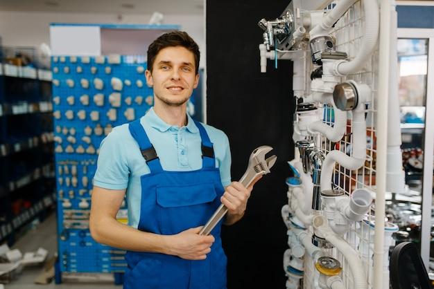 Сантехник с трубными ключами позирует у витрины, выбор сантехнического магазина. человек, покупающий сантехнические инструменты и оборудование в магазине