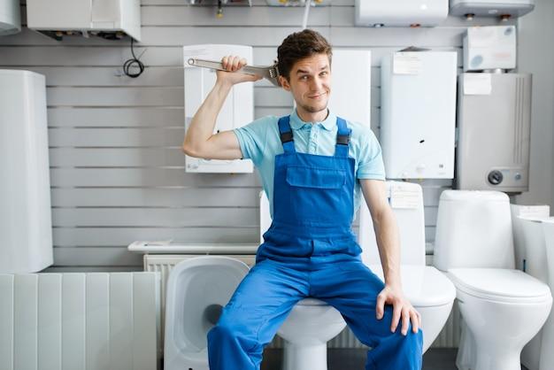 配管工店のショーケースのトイレにパイプレンチを置いた配管工。店で衛生工学の道具や設備を買う男