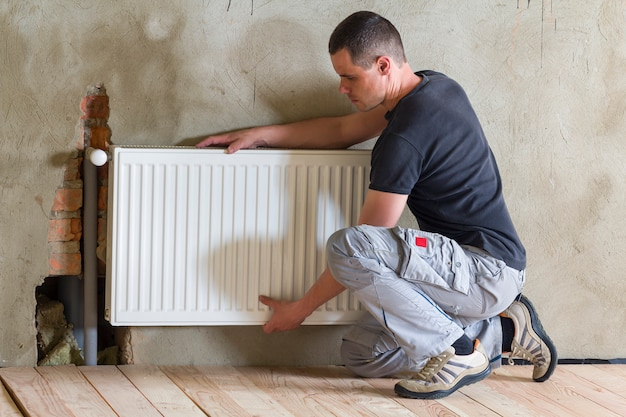 Plumber worker installing heating radiator in an empty room of a newly built apartment or house.