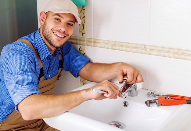 Plumber working on sink in the small bathroom at home