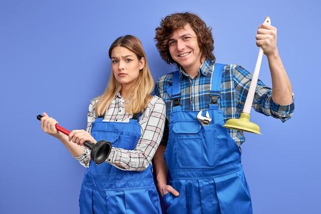 プランジャーを手に持って、シンクとバスルームを修理する準備ができている配管工