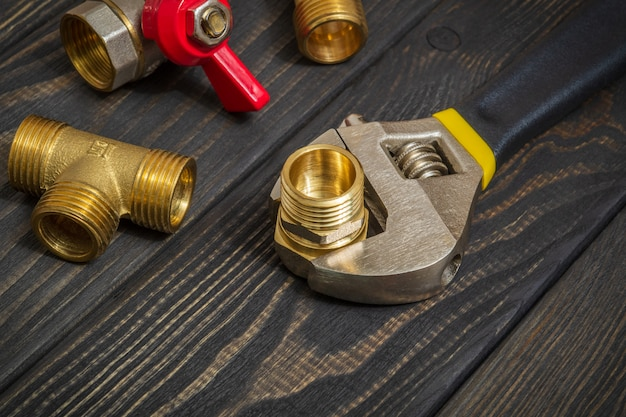 Plumbing brass fittings and adjustable spanner closeup on black wooden boards during repair or replacement of spare parts